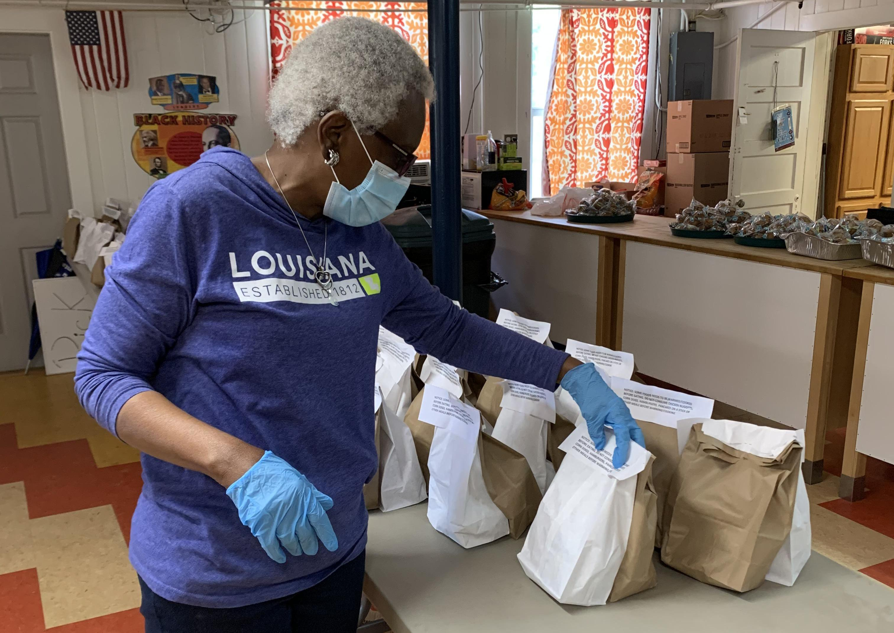 Volunteers at the Thensted Center in Grand Coteau, Louisiana, prepare sack lunches for children in the area during the COVIS-19 pandemic